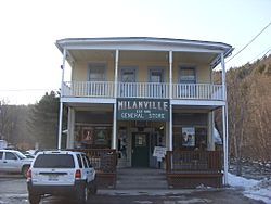 "Old-fashioned, refurbished, two-story building, with yellow and blue paint and white siding. A sign on the front of the building reads ""MILANVILLE GENERAL STORE, EST. 1850,"" and there a few cars parked in front on it."