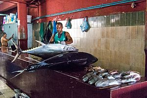 A fishmonger prepares to clean and butcher a pair of large fish in Malé