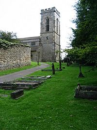 The east end of a stone church is seen through a graveyard from the north. On the right is a battlemented tower and the nave extends to the left