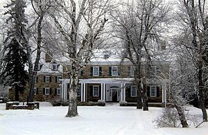 A snow-covered 2-story house with dormer windows on the roof and a porch on the ground floor. The stone house has several large trees in front.
