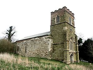 A stone church seen from the northwest. In the foreground is a battlemented tower with a west door and clock with the nave and chancel beyond.